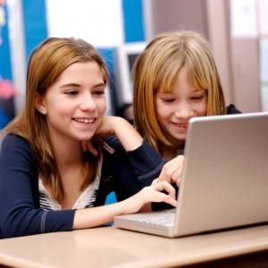 Two young girls working on a laptop in the classroom